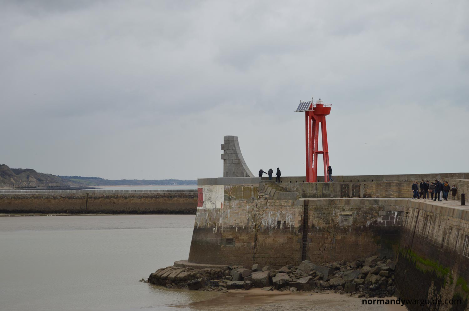 Monument To The Liberation Of Europe On PortenBessin Harbour Wall - Location port en bessin